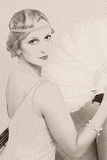 Old photo twenties style woman. Old photo effect of a vintage twenties woman with feather fan Royalty Free Stock Photography