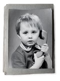 Old photo in an vintage photoalbum. Old photo of little boy with phone in an vintage photoalbum (isolated stock photos