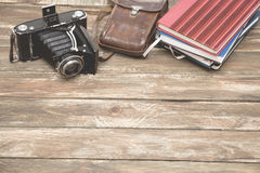 Old photocamera with leather case, notebooks on vintage wood background Stock Images