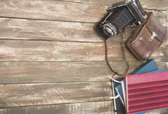 Old photocamera with leather case, notebooks on vintage wood background Royalty Free Stock Photos