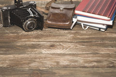 Old photocamera with leather case, notebooks on vintage wood background Stock Photo