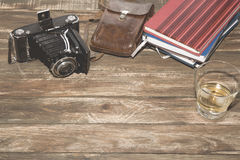 Old photocamera with leather case, notebooks on vintage wood background. Old-fashioned photocamera with leather case and notebooks on vintage wood background stock image