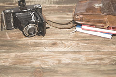 Old photocamera with leather case, notebooks on vintage wood background. Old-fashioned photocamera with leather case and notebooks on vintage wood background royalty free stock image
