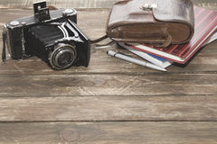 Old photocamera with leather case, notebooks on vintage wood background. Old-fashioned photocamera with leather case and notebooks on vintage wood background stock photography