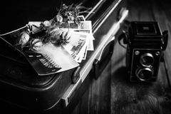 Old photographs, a camera and dried flowers. Black and white Royalty Free Stock Photo