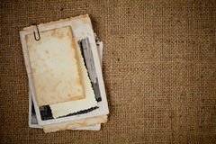 Old photos bunch over burlap texture as template Stock Photography
