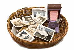Old Photos and Camera. A collection of old family photos and a colorful camera in a wicker basket royalty free stock photo