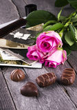 Old photos pink roses and chocolate on a dark wooden background Stock Images