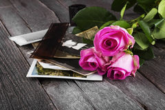 Old photos pink roses and chocolate on a dark wooden background Stock Photos