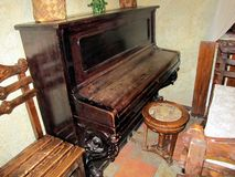 Old piano in the ancient Russian house. The room is aged Russian style royalty free stock image