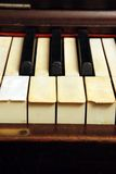 Old piano with ivory keys broken and scratched Stock Images