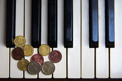 Old piano keys and coins Stock Image