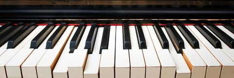 Old piano keys, pressed by themselves. Wide angle front view Royalty Free Stock Photo