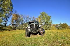 Old pickup left in a pasture with sprayer booms extended Stock Photos