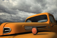 Old Pickup Truck. Old yellow pickup truck with clouds Stock Images