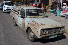 Old pickup truck parked alongside new vehicles. Parys South Africa - a dilapidated old pickup truck parked alongside newer model vehicles on a street in this Royalty Free Stock Image