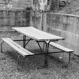 Old picnic table in corner of concrete wall. Black and white photo of picnic table in corner of concrete wall royalty free stock photography