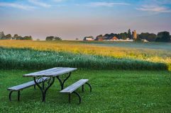 An old picnic table in a lawn looking toward a farm across an alfalfa field. The sky is humid and hazy royalty free stock photo