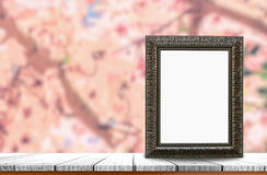 Old picture frame. With blank space put on wooden table top and flower nature background use for products of pictures or texts display Royalty Free Stock Images