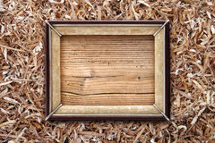 Old picture frame on a wood shavings  background Stock Image