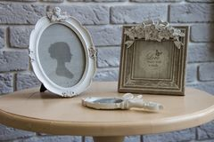Old picture frames, lying mirror on the table with grey brick wall background, closeup Royalty Free Stock Images