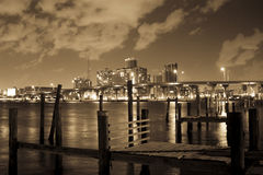 Wooden pier in Miami. A little wooden old and rotten pier with the lights of the Miami city as a background stock image