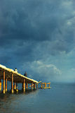 Old pier at beach. And fishers Stock Photography