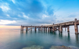 Old pier bridge in beautiful morning sunrise and calmness seascape. At Khao Laem Ya National park, Rayong Province, Eastern Thailand Stock Photos
