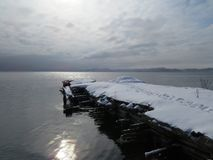 Old pier covered with snow in the Gulf of the Pacific ocean. stock photos