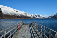Old pier going into the deep blue fjord with snowy mountain backdrop Stock Photography