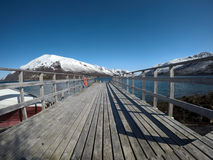 Old pier going into the deep blue fjord with snowy mountain backdrop Royalty Free Stock Images