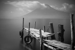 Old pier on lake. Old rickety wooden pier juts out into lake Atitlan (Guatemala) with volcano in background.  Black and White Stock Images