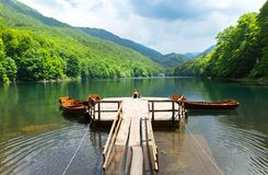 Old pier on mountain lake. Old pier and boats on mountain lake. Biograd lake, Montenegro royalty free stock photography