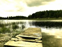 Old pier near the lake. Bleak landscape - the old pier with broken planks leads to the lake. In the background lies a forest royalty free stock photography