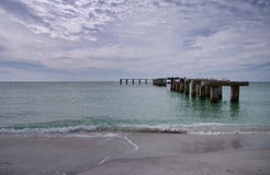 Old pier pilings at Boca Grande Pass Beach Stock Images