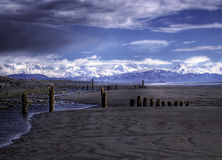 Old pier pillars on an Alaskan Beach with clouds Royalty Free Stock Images