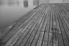 Old grey pier and reflection of buildings on river stock photography