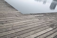 Grey pier and reflection of buildings on river stock image