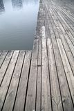 Grey pier and reflection of buildings on river picture Royalty Free Stock Photo