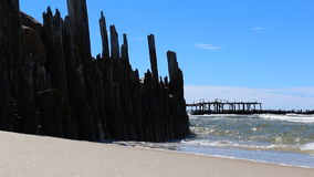 Old pier ruins, sandy beach, sea and blue sky Royalty Free Stock Image