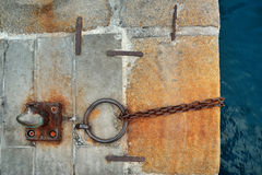 Old pier with a rusty chain and ring. On stone slabs Royalty Free Stock Photo