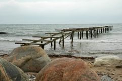 Old pier in the sea. With boulders on the foreground royalty free stock photos