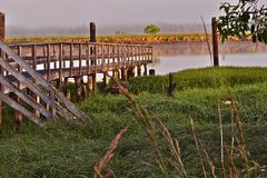 Old pier on a slough pacific coast. Slack water on a slough with an old pier and reflection of the bank in the water and a foggy misty back drop Royalty Free Stock Image