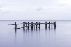 Old pier structure falling down, posts standing in tranquil lake Stock Photos