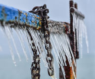 Old pier in winter with icicles. Part of an old pier covered with ice/icicles and with fragment of anchor chain. Selective focus royalty free stock image