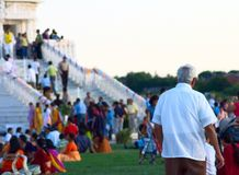Old pilgrim. A white haired man in a white shirt walking toward the stairs of a temple, lots of colorful dressed people in the background Stock Image