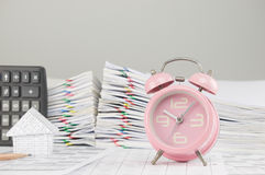 Old pink alarm clock have blur house as background. Old pink alarm clock on finance account have blur house and calculator with pencil and pile overload Stock Images
