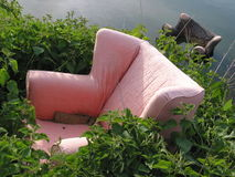 Old pink armchair dumped in green weeds. A pink armchair dumped in weeds with a second chair in a pond Stock Images