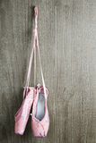 Old pink ballet shoes. Old used pink ballet shoes hanging on wooden background Stock Images