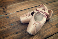 Old pink ballet shoes on a wooden floor Royalty Free Stock Image
